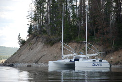 catamaran sailboat anchored near woods