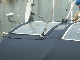 marine solar system kit with semi flexible marine solar panels mounted with bolts to bimini canvas on sailboat