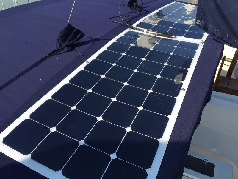 Two 110 Watt Semi-flexible Solar Panels Attached to sailboat Dodger using 6 bolt solar panel mounting system on boat