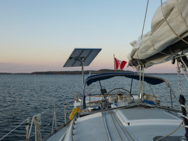 140 watt rigid solar panel mounted to top of pole on stern 32 foot sailboat
