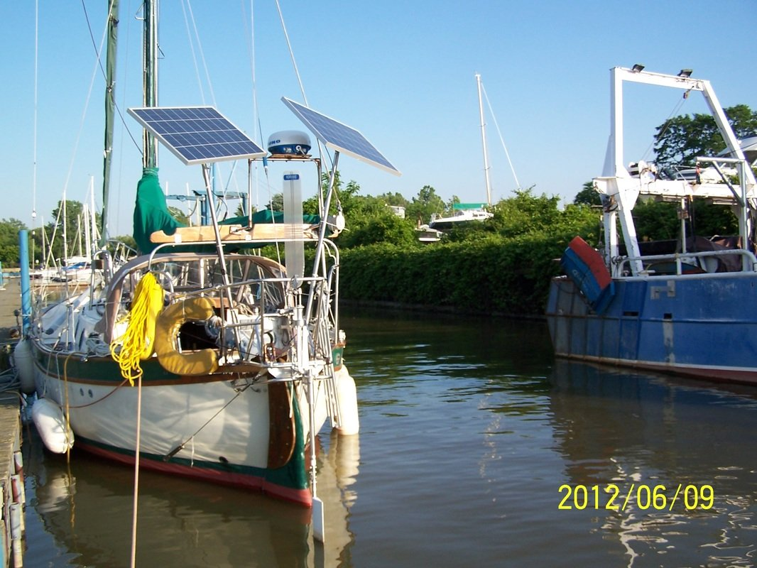 2 rigid marine solar panels mounted top of poles on sailboat