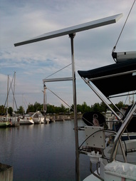 rigid marine solar panel mounted top of pole on sailboat with outboard motor lifting crane accessory attached