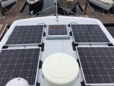 4 rigid marine solar panels mounted to roof of boat
