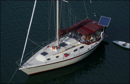 Sailboat with rigid marine solar panel mounted with top of pole solar mounting system